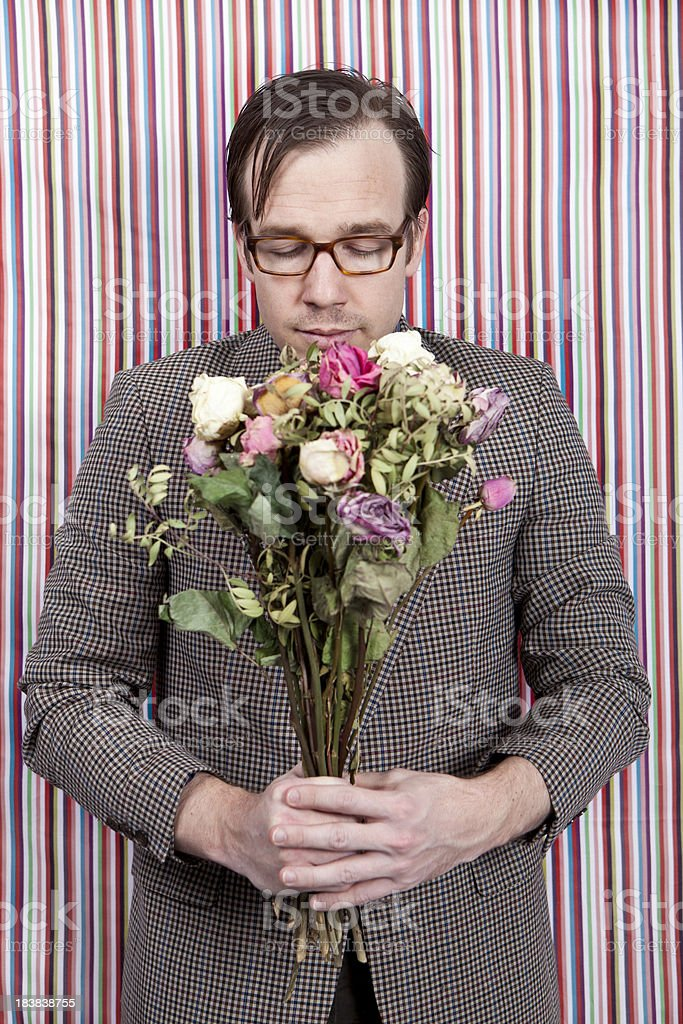 Nerdy businessman smelling a bunch of flowers stock photo