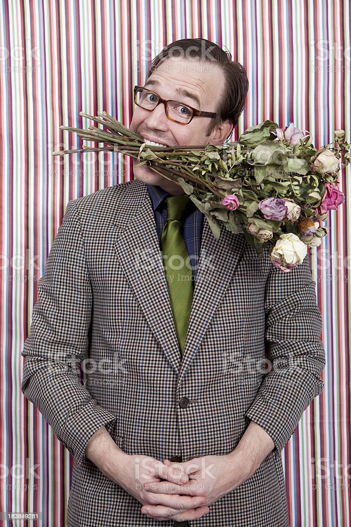 Nerdy businessman with a bunch of flowers in his mouth! stock photo
