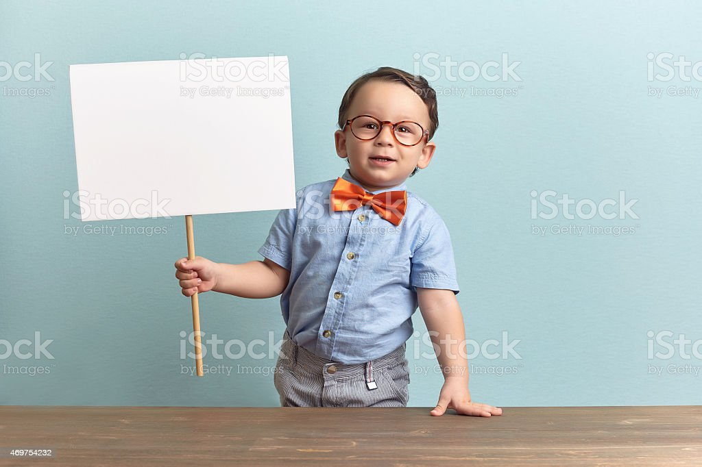 Nerdy child holding a blank sign in a classroom stock photo