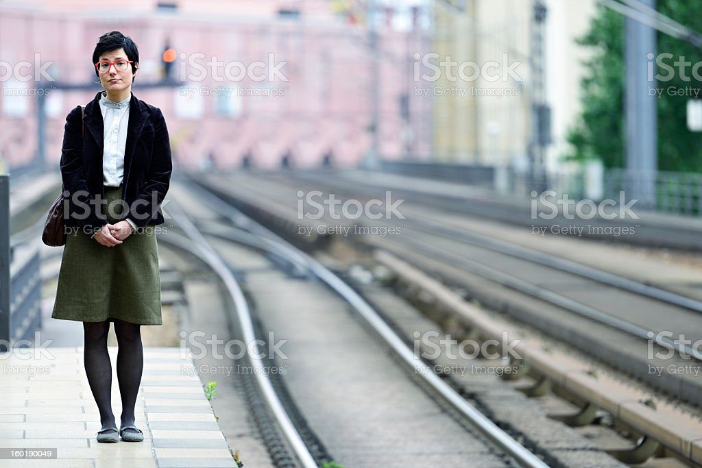 Nerdy Girl Standing Lost on Platform Waiting for the Train royalty-free stock photo