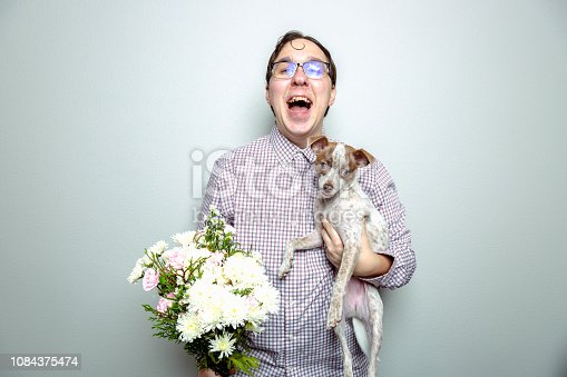 Nerdy guy holding a lap dog and flowers because guys with puppy dogs get ladies.