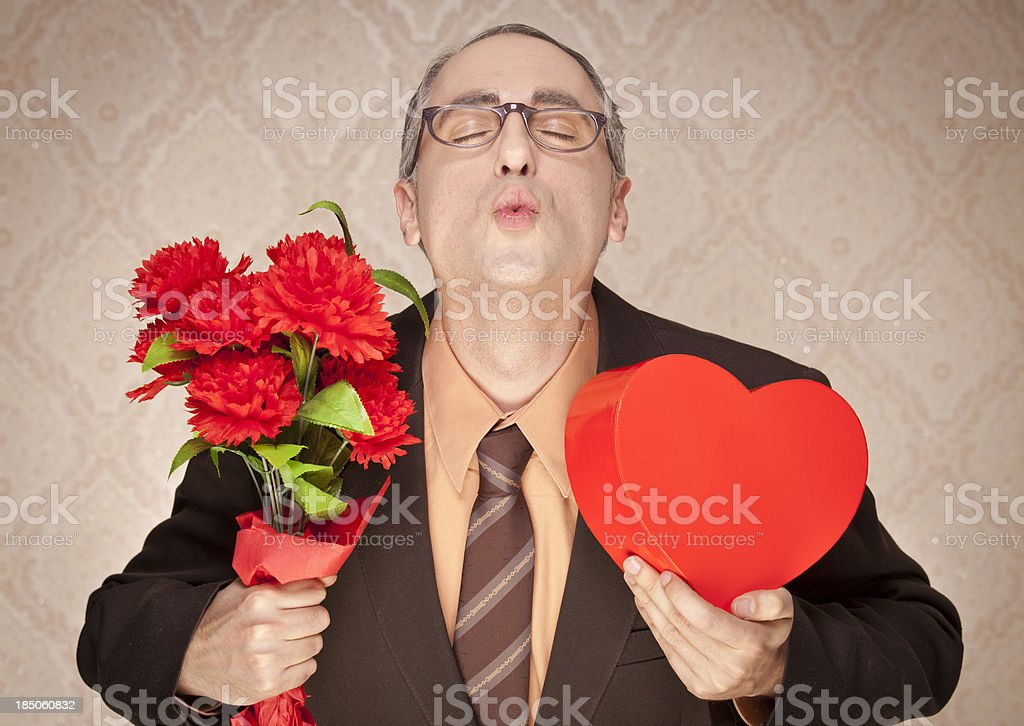 Nerdy guy in love holding flowers and candy heart box stock photo