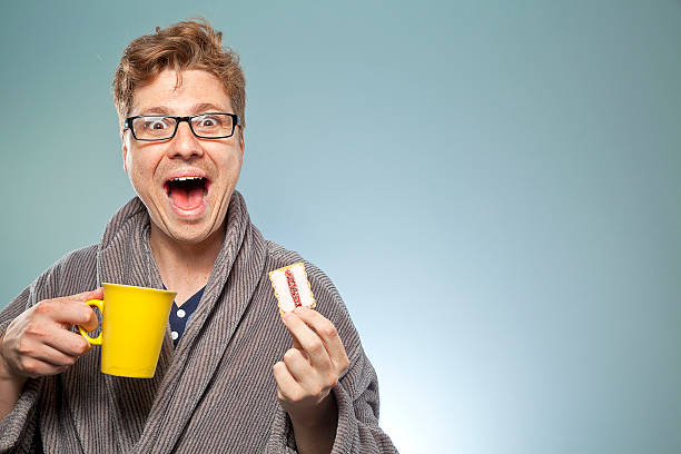 nerdy guy smiling with a coffee and biscuit - nerd boy eating stock photos and pictures