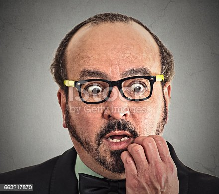 istock nerdy guy with glasses biting his nails looking at you 663217870