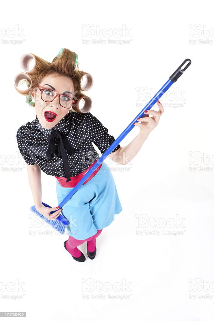 Nerdy housewife with glasses having fun with broom royalty-free stock photo