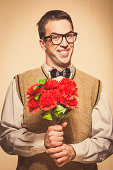 Nerdy looking shy guy holding flowers, against a vintage background