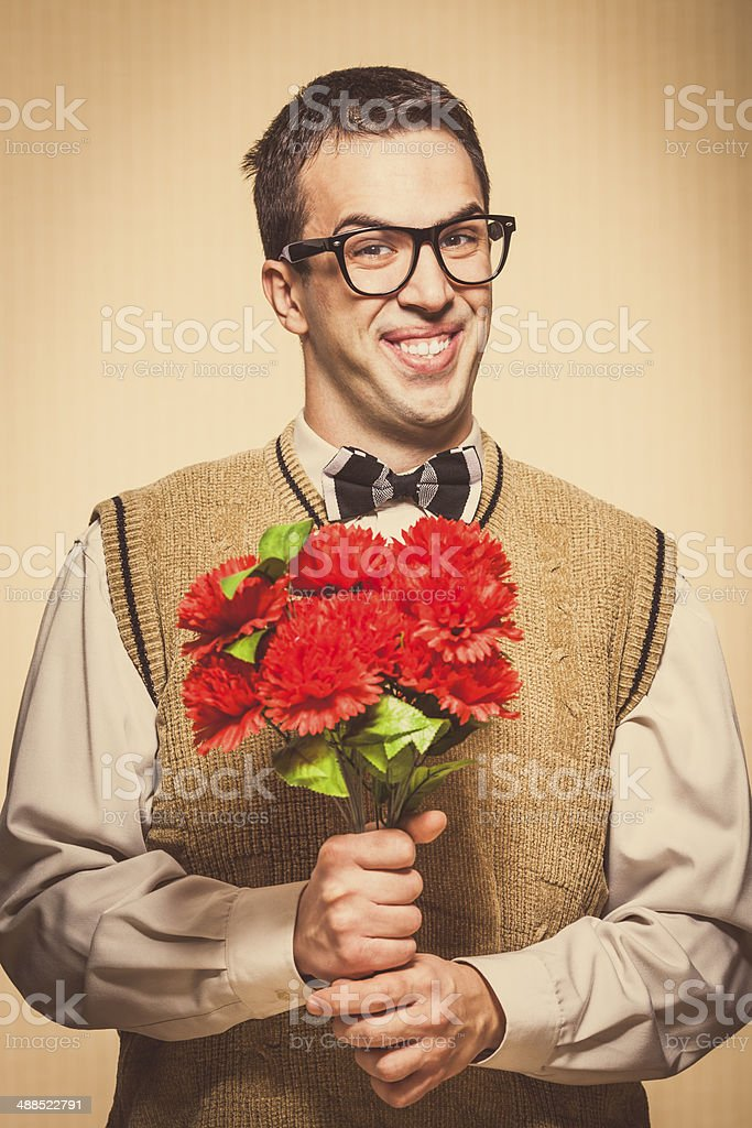 Nerdy looking young man holding flowers stock photo