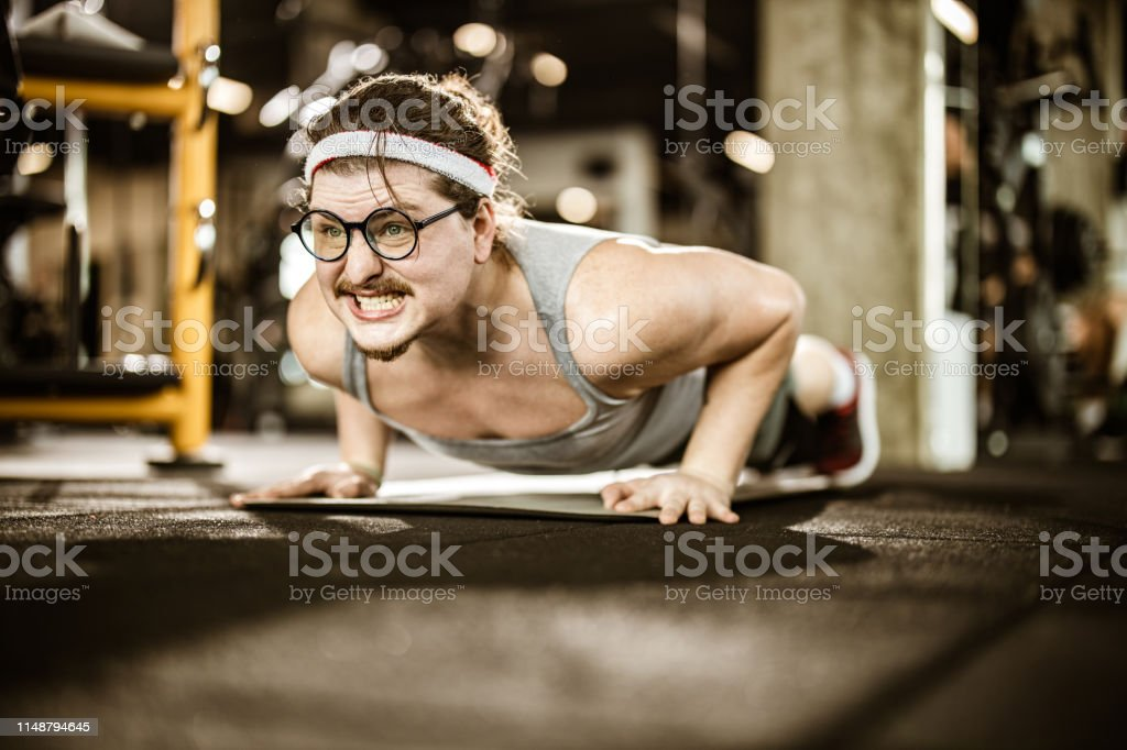 Funny athletic man making an effort while doing push-ups in a health...