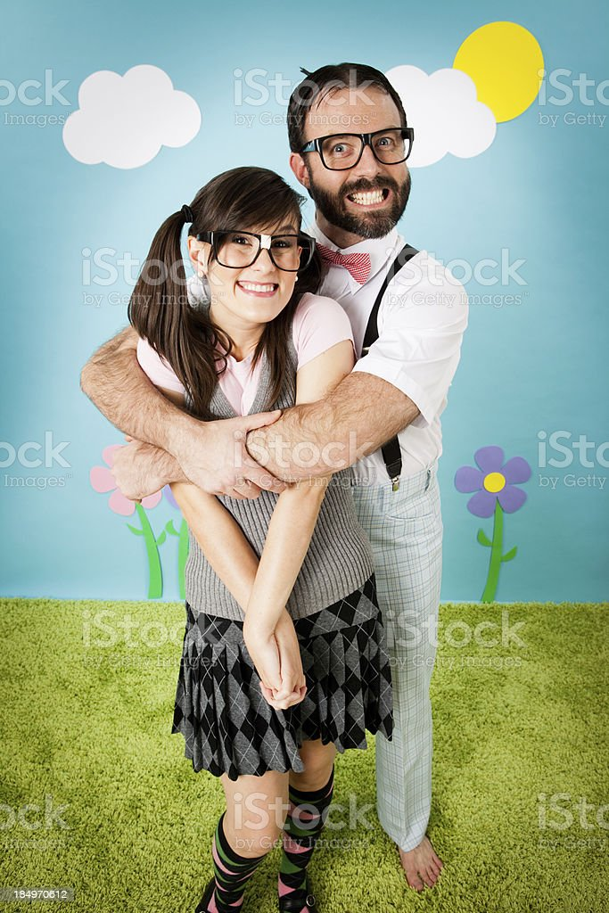 Nerdy Man Embracing Young Woman in Whimsical Outdoor Setting stock photo