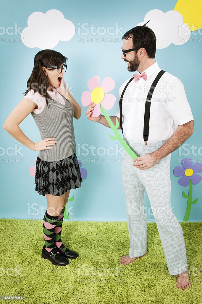 Nerdy Man Giving Girlfriend Large Flower in Whimsical, Outdoor World stock photo