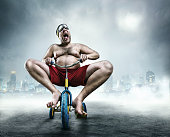 istock Nerdy man riding a small bicycle 530088629