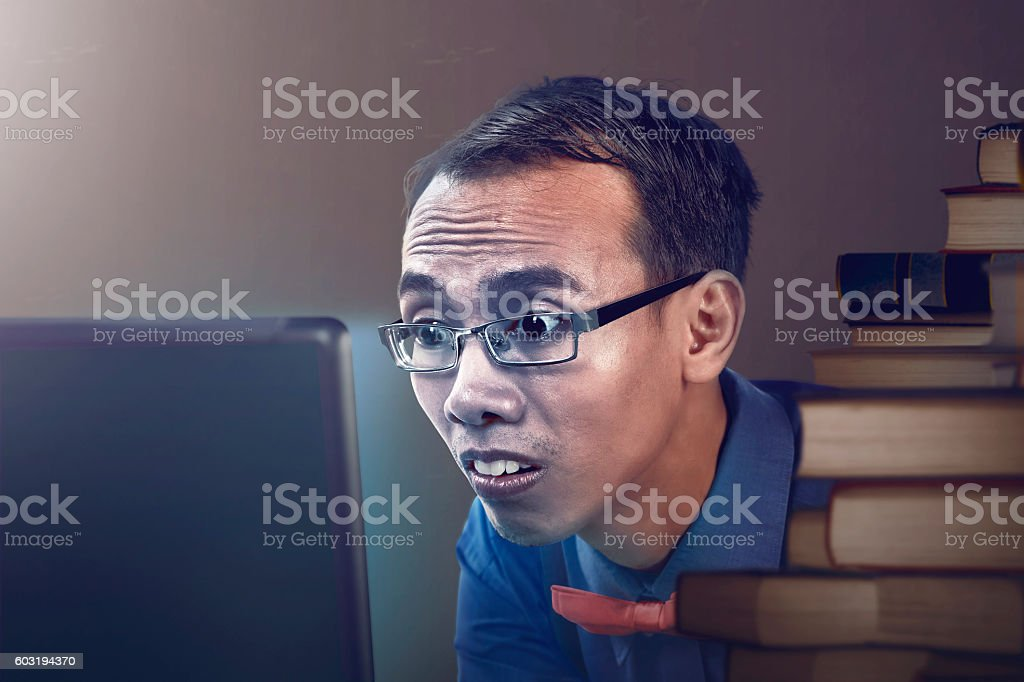 Nerdy man studying with laptop stock photo