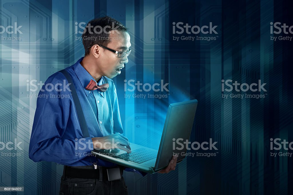 Nerdy man using laptop stock photo