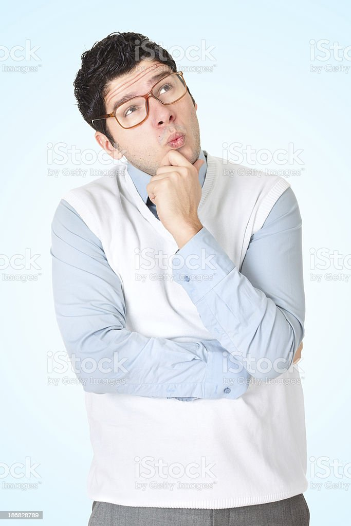 Nerdy man with glasses holding hand on chin and thinking stock photo