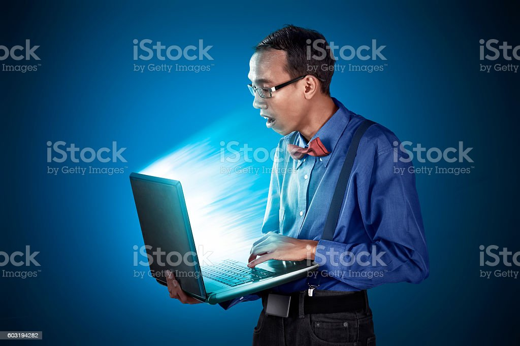 Nerdy man with laptop use standing position stock photo