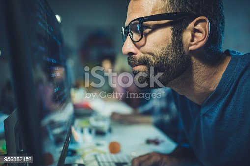 Young nerdy computer programmer working on desktop PC in the office.