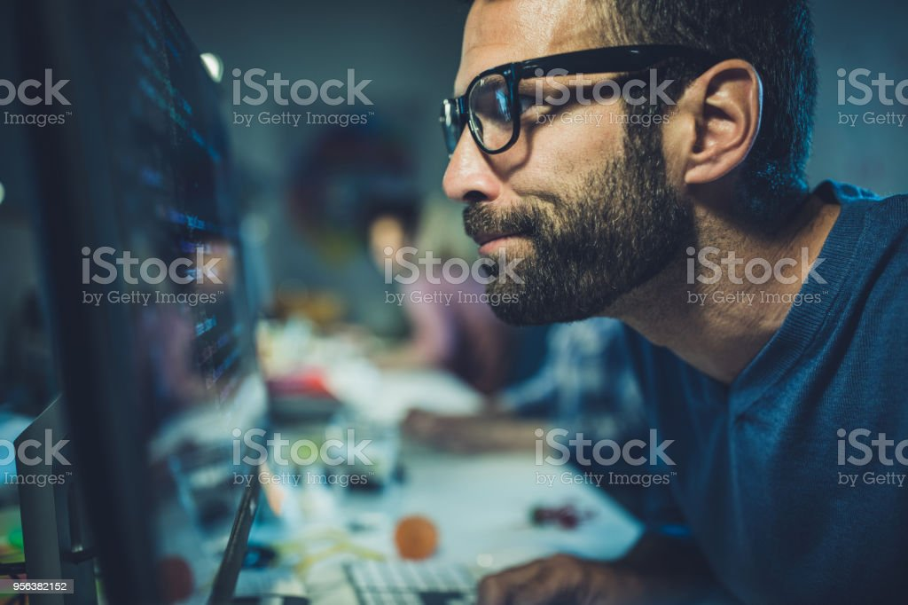 Nerdy programmer analyzing codes on desktop PC in the office. stock photo