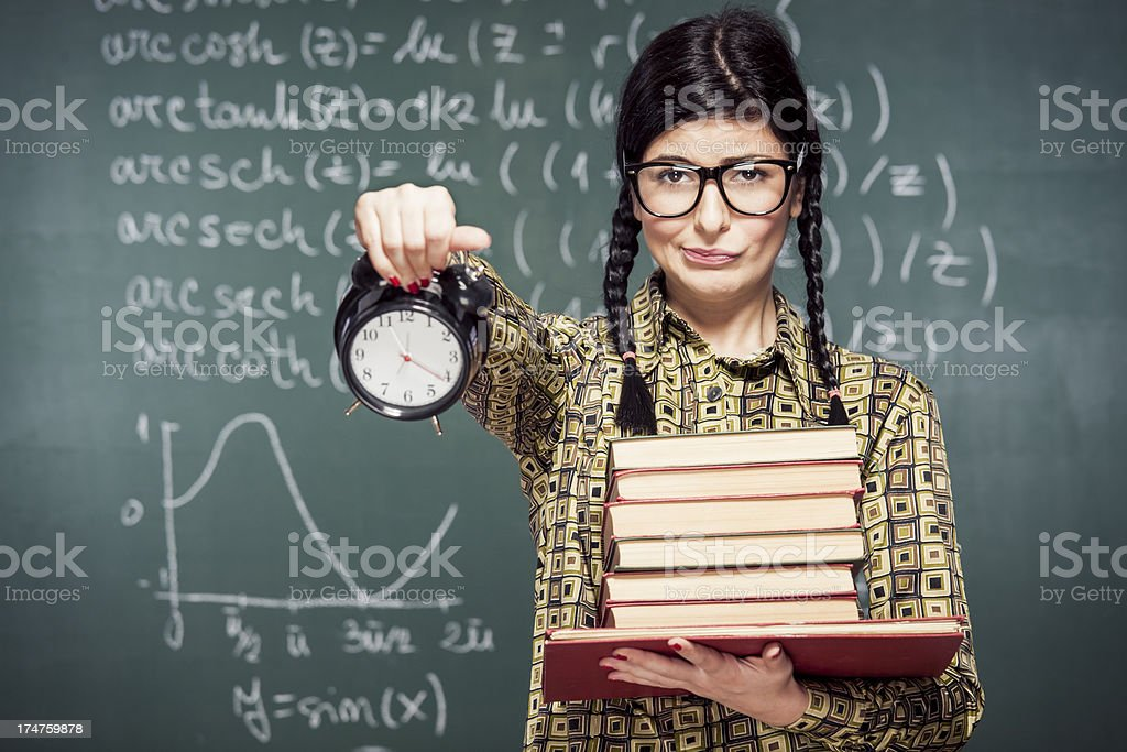 Nerdy student in front of chalkboard stock photo