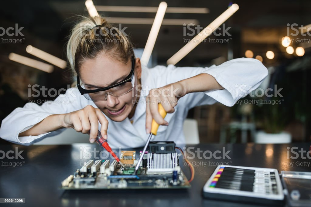 Young nerdy college student making a face while trying to fix...