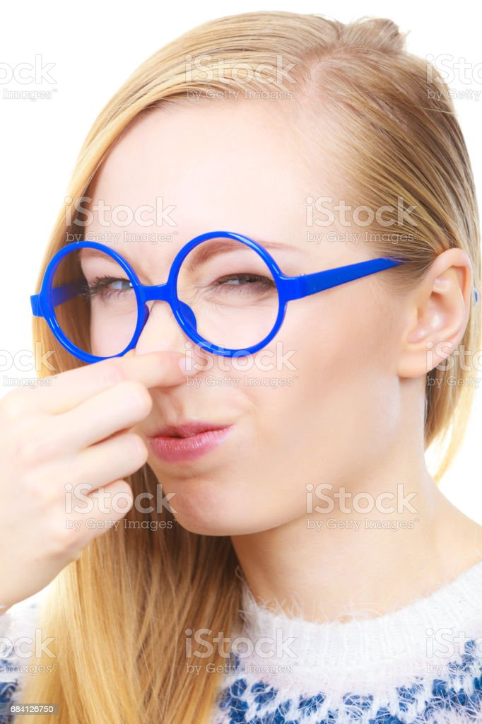 Nerdy woman holding nose smelling bad scent stock photo