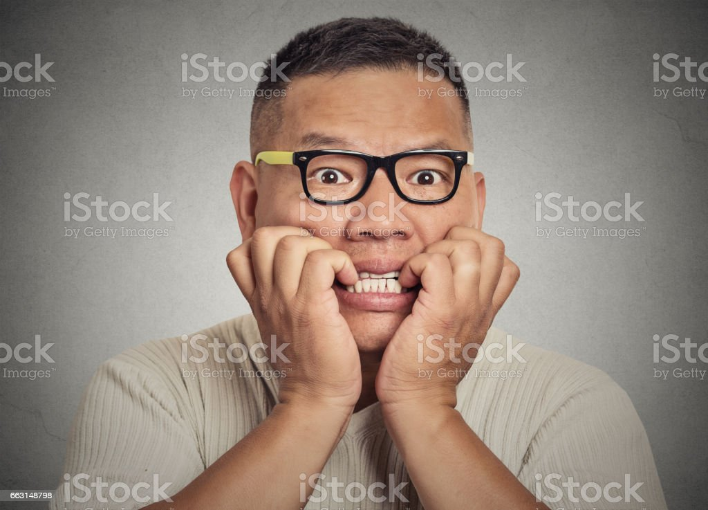 nerdy young guy with glasses biting his nails looking at you stock photo
