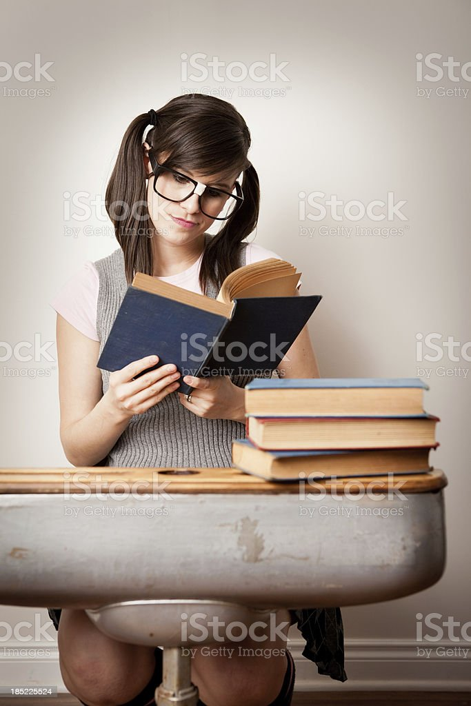 Nerdy Young Woman Student Reading Book at School Desk royalty-free stock photo