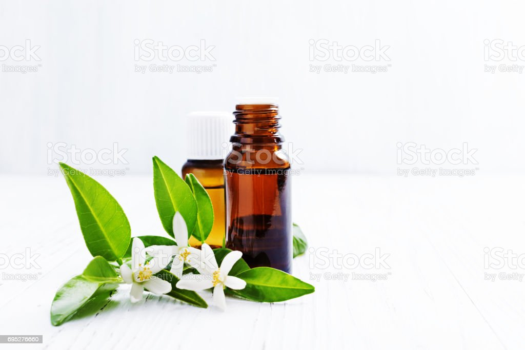 Neroli (Citrus aurantium) essential oil in a brown glass bottle with fresh white  flowers on ligth background. Selective focus. stock photo