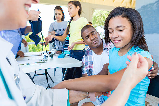 Nervous African American Girl about to get a flu shot Nervous African American girl looking down at the ground right before the doctor gives her a flu shot or vaccination. Her father is concerned and kneeling beside her. There is a little girl getting a health examination behind her. tetanus stock pictures, royalty-free photos & images