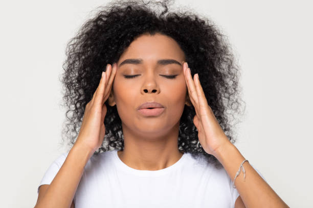 Nervous african woman breathing calming down trying to relieve stress Nervous african woman breathing calming down relieving headache or managing stress, black girl feeling stressed self-soothing massaging temples exhaling isolated on white grey studio blank background relief emotion stock pictures, royalty-free photos & images