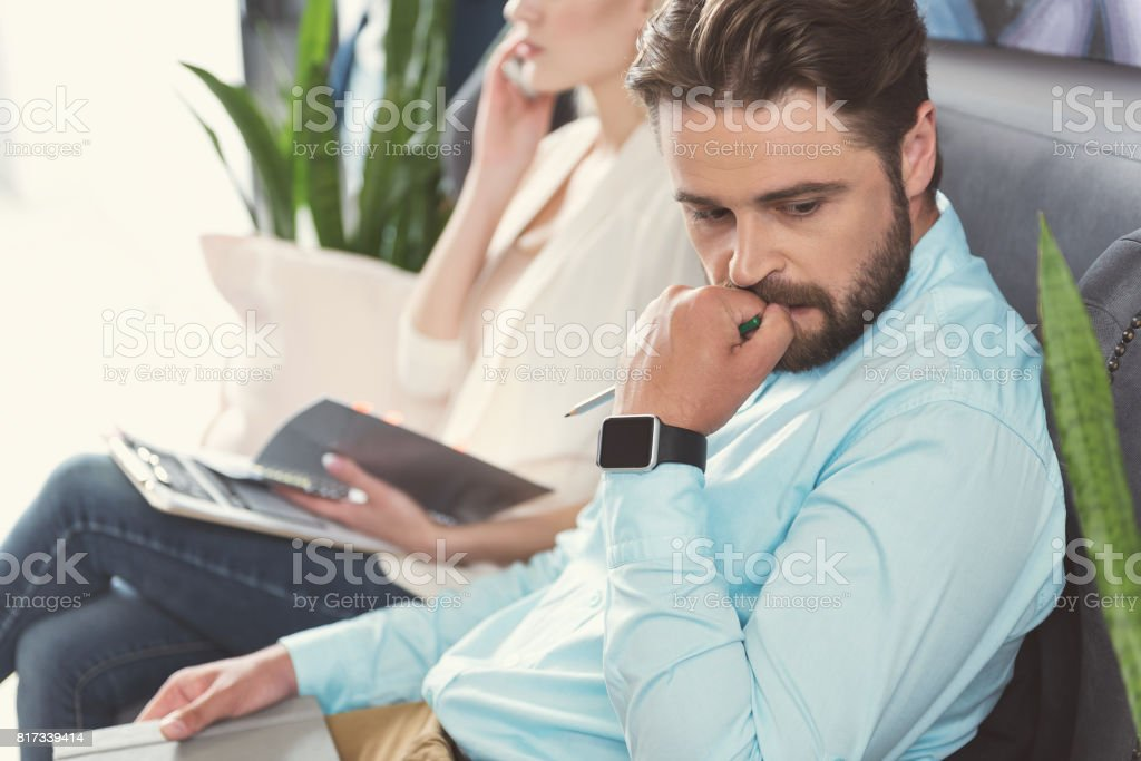 Nervous bearded guy waiting in queue for job talk indoor stock photo