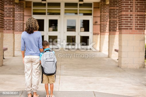 Back to school... Cute, African descent little boy clings to his mom for reassurance on the first day of school.