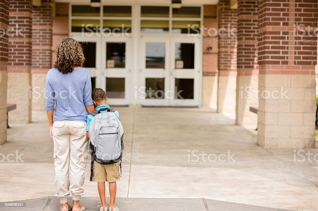 Nervous boy. First day of school.  Holds on to mom. stock photo