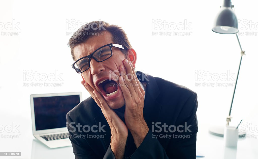 Young businessman screaming in frustration at office