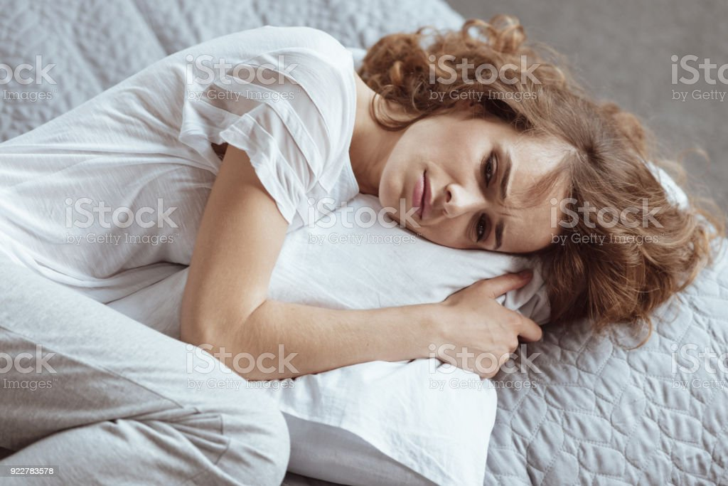 Nervous brunette lady embracing pillow and thinning about something depressing stock photo