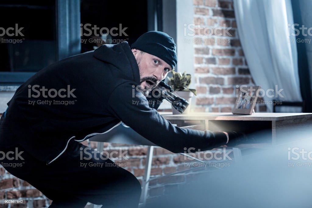 Assaltante nervoso à procura de documentos na tabela - foto de acervo