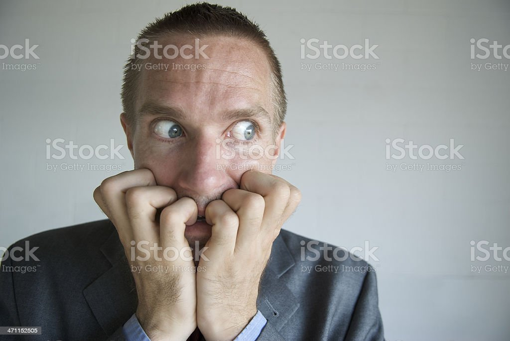Nervous Businessman Biting Fingers with Wide Eyes royalty-free stock photo