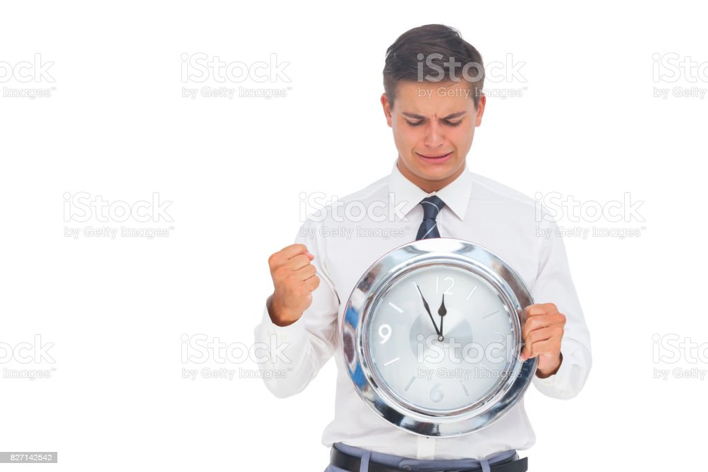 nervous businessman holding and looking at clock stock photo more