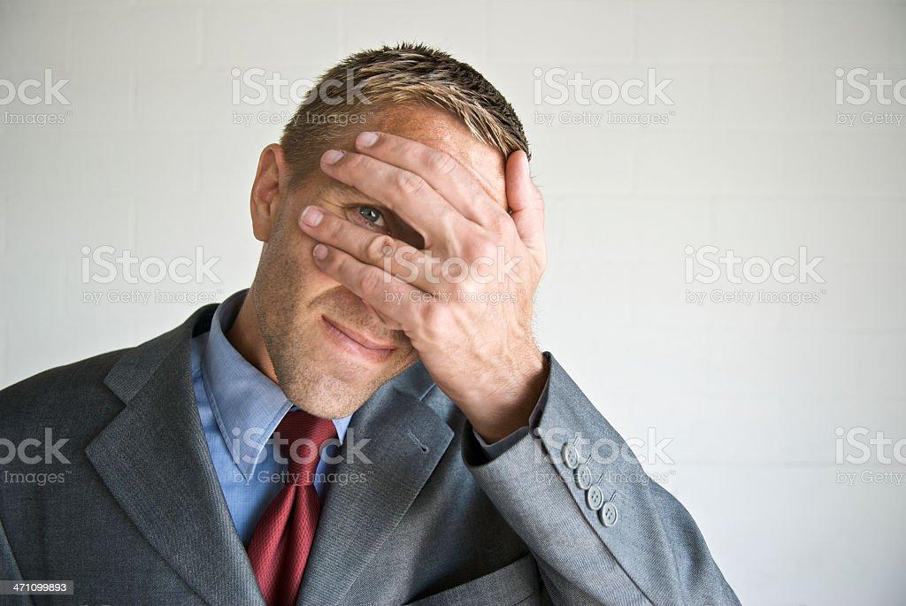 Nervous Businessman Peeking Through Fingers stock photo