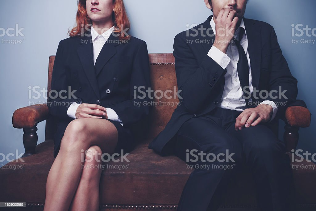 A nervous businessman sitting next to confident woman stock photo