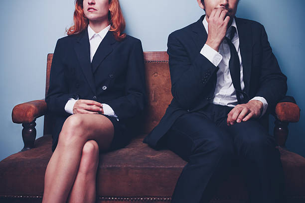 A nervous businessman sitting next to confident woman Nervous businessman is biting his nails while sitting next to a confident businesswoman as they are both waiting to be interviewed for the same job interview nerves stock pictures, royalty-free photos & images