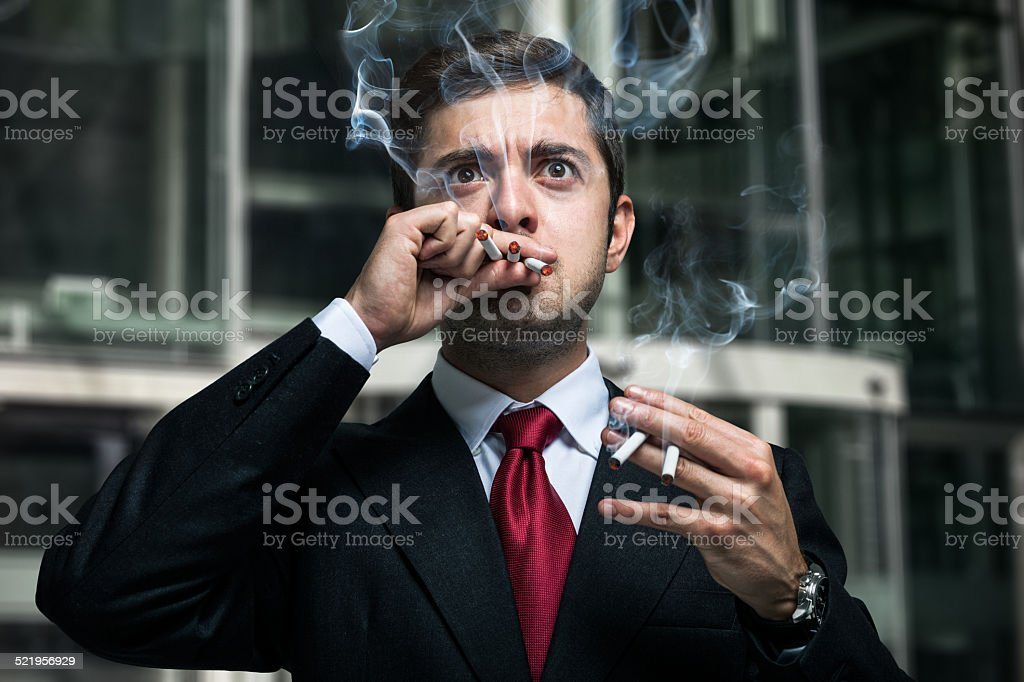 Nervous businessman smoking many cigarettes at once stock photo