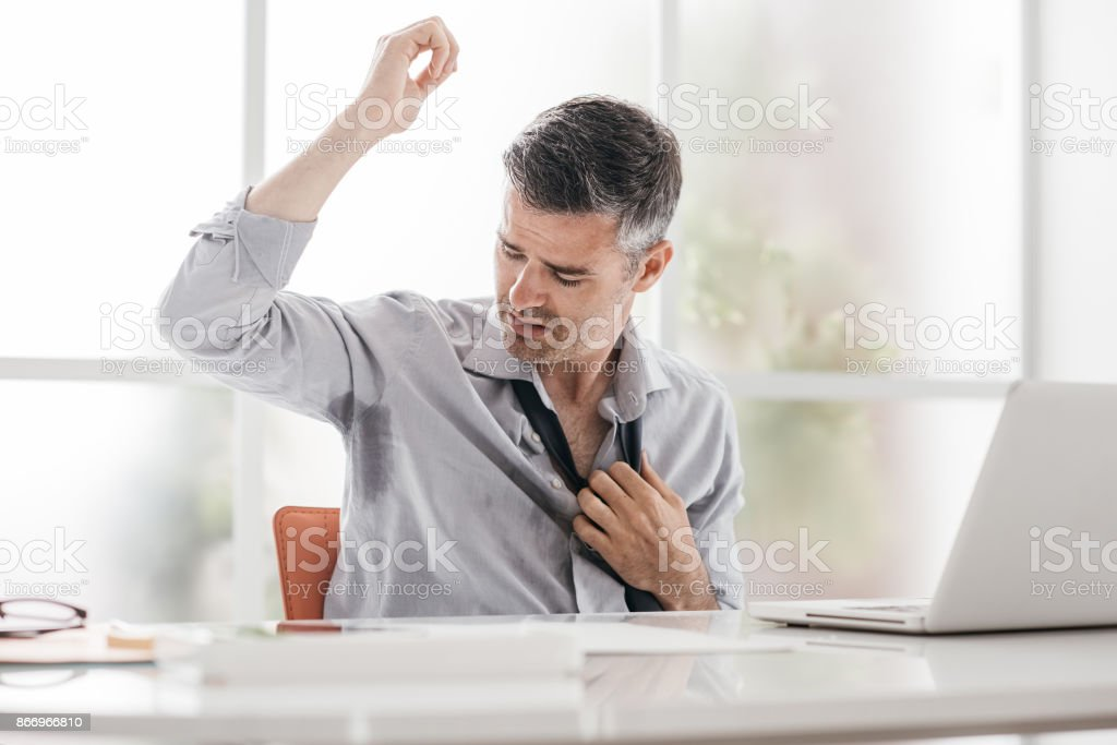 Nervous businessman sweating stock photo