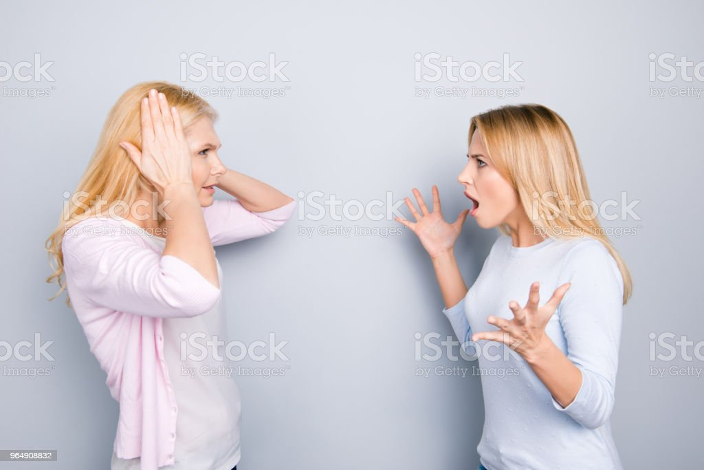 Nervous irritated frustrated daughter screaming at her depressed mom closing covering ears with palms ignoring arguments gesturing with hands isolated on grey background royalty-free stock photo