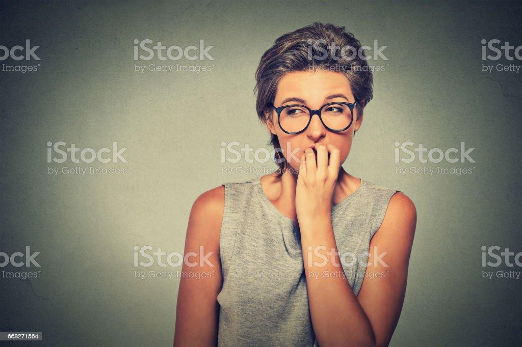 nervous looking woman biting her fingernails craving something anxious foto stock royalty-free