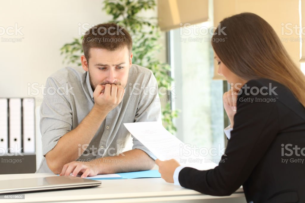 Nervous man in a job interview stock photo