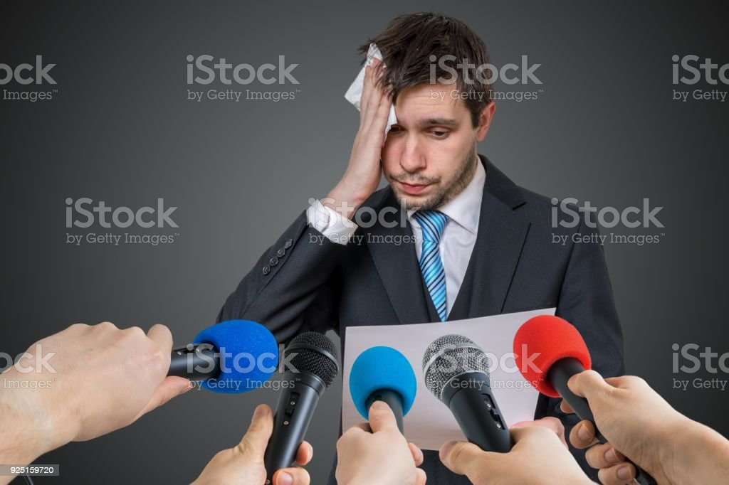 Nervous man is afraid of public speech and sweating. Many microphones in front. stock photo
