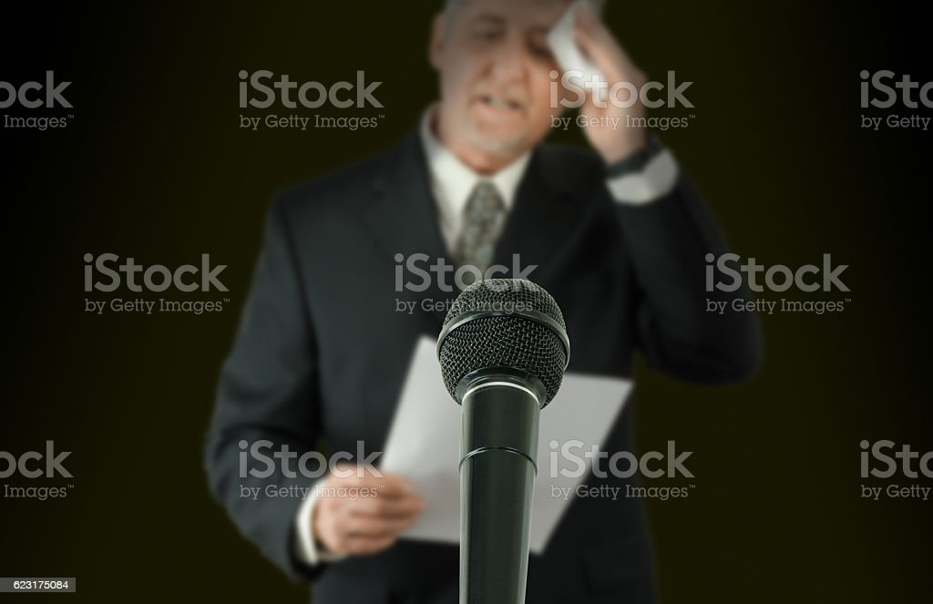 Nervous public speaker or politician wiping brow microphone in focus - Photo