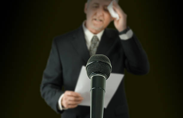 Nervous public speaker or politician wiping brow microphone in focus stock photo