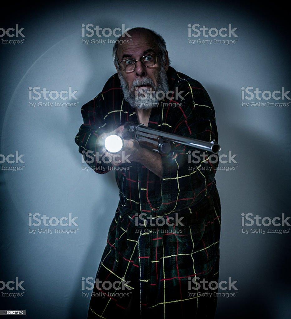 Nervous Senior Man Pointing Shotgun and Flashlight in Dark Room stock photo