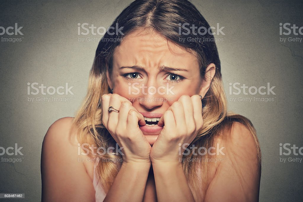 nervous stressed woman biting fingernails looking anxiously stock photo